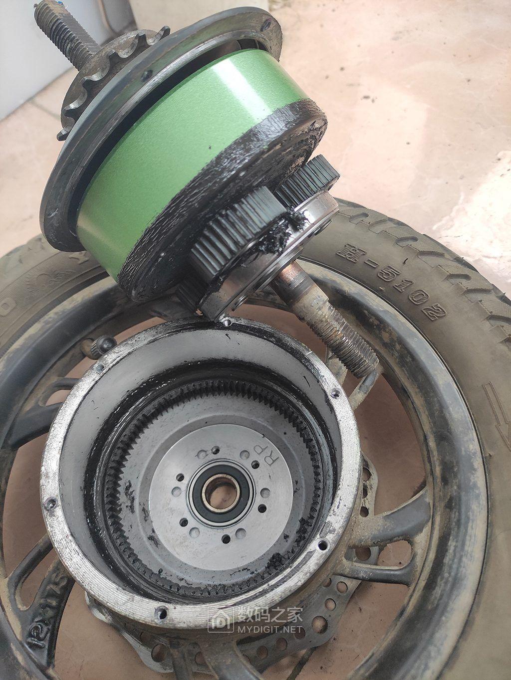 010把六个螺丝拆下来后,找一块木板什么的垫在地上,拿着轮胎,把碟刹那面的后轴往木.jpg